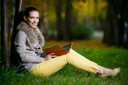 Fashion woman using a tablet computer outside in evening park. Student sitting on green grass over tree. photo