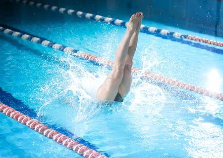 Portrait eines weiblichen Schwimmer, dass Springen und Tauchen in Sportinnenpool. Sportliche Frau. Standard-Bild