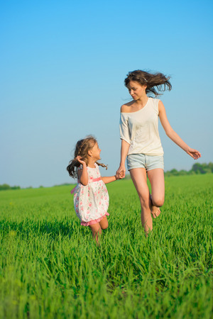 Young happy girls running down green wheat field with her friend together photo