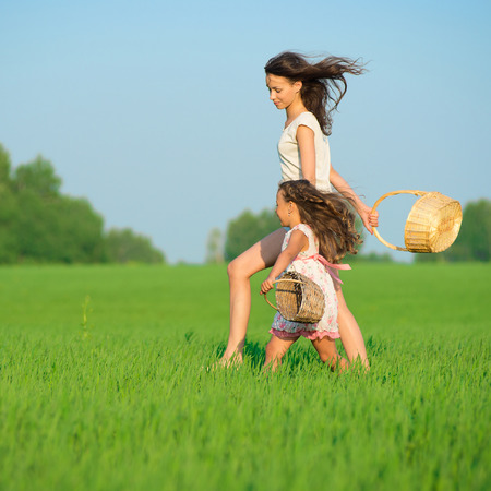Young happy girls running with basket at green wheat field with her friend together photo