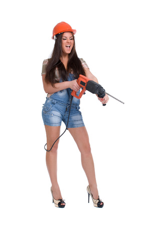 coverall: Young female dressed in jeans and orange helmet holding hammer electric drill on White isolated background.