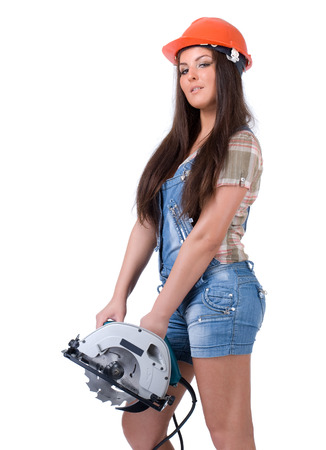 Young female dressed in jeans and orange helmet holding an electric circular disk saw On a white isolated background