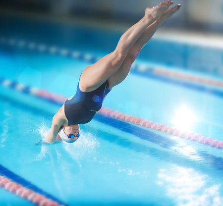 Portrait of a female swimmer, that jumping and diving into indoor sport swimming pool