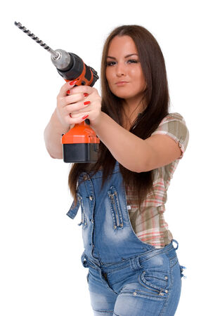 Young female dressed in jeans holding a cordless electric drill on a white isolated background  photo