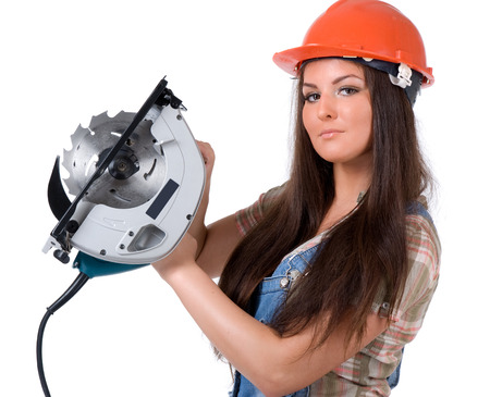 Young female dressed in jeans and orange helmet holding an electric circular disk saw On a white isolated background photo