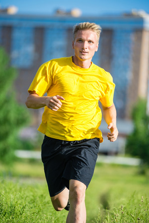 Running man jogging in city street park at beautiful summer\ day. Sport fitness model caucasian ethnicity training\ outdoor.