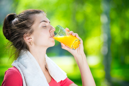 Young woman drinking fresh orange juice after sport fitness exercise at green summer park
