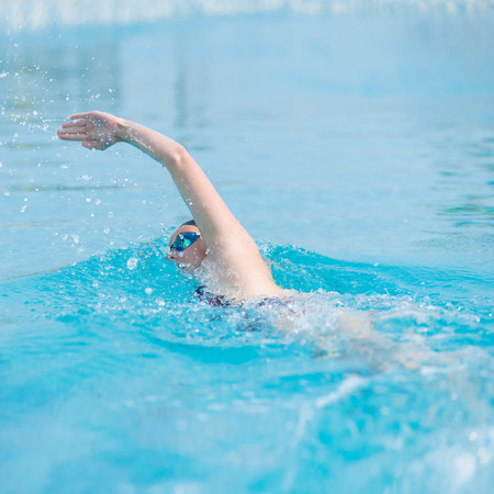 Young girl in goggles and cap swimming front crawl stroke style in the blue water pool photo