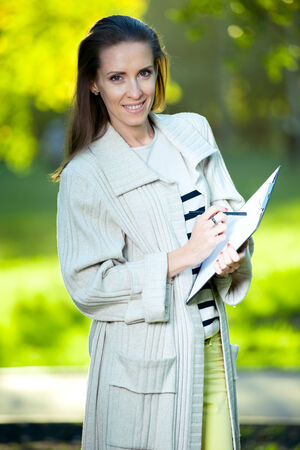 Portrait of smiling business woman with paper folder and pad, against green city park background. Student. photo