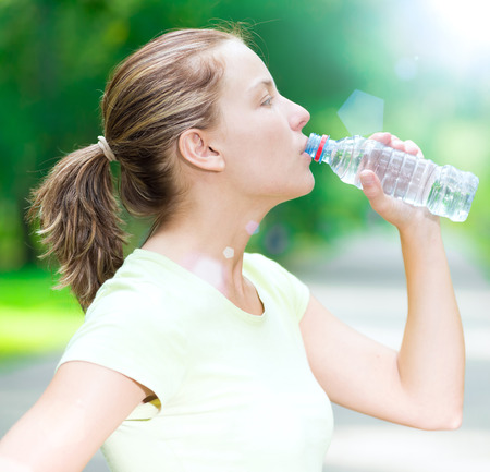 water park: Young beautiful woman drinking cold mineral water from a bottle  after sport fitness exercise at green summer park