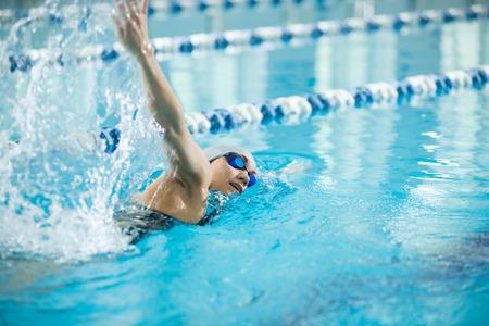 ゴーグルと青い水屋内レース プールでクロールのストローク スタイルを水泳キャップの若い女性