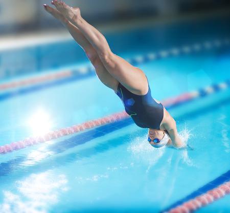 dive: Retrato de un nadador femenino, que saltar y zambullirse en la piscina cubierta climatizada deporte. Mujer deportiva.