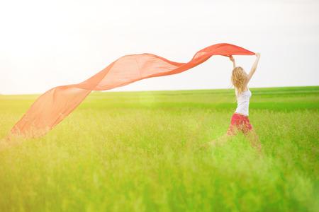 Jovencita runing con tejido en el campo verde. Hermosa mujer feliz caminando en el prado rural verano. Retrato al aire libre del verano de la mujer bonita de estilo deportivo que salta con la tela. Hermosa chica tan en forma. Modelo slim caucásica al aire libre etnia sexy.