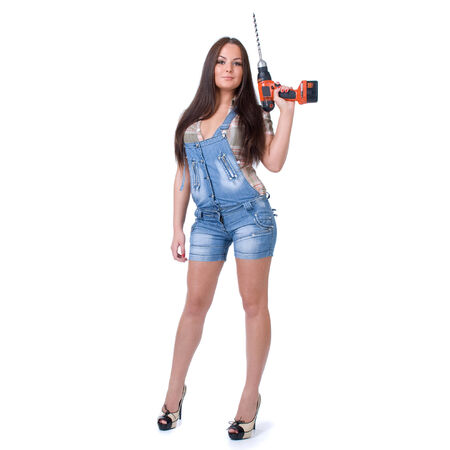 Young sexy female dressed in jeans  holding a cordless electric drill on a white isolated background photo