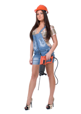 Young sexy female dressed in jeans and orange helmet holding hammer  electric drill. White isolated background. photo