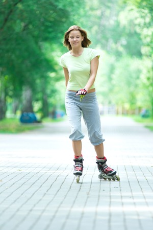 inline: Roller skating sporty girl in park rollerblading on inline skates.  Caucasian woman in outdoor fitness activities.