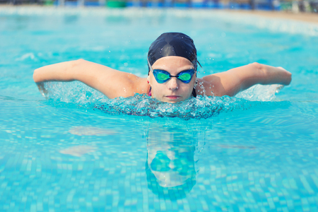 swimming animal: Young girl in goggles and cap swimming butterfly stroke style in the blue water pool Stock Photo