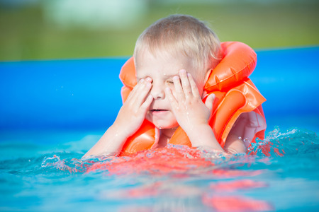 life jacket: Pretty little boy in swimming pool. Snorking in the outdoor pool in orange life jacket
