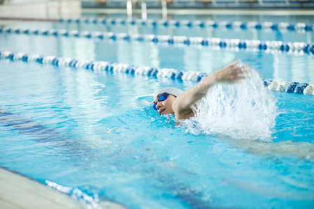 swimming race: Young woman in goggles and cap swimming front crawl stroke style in the blue water indoor race pool