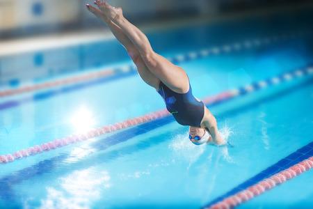gente saltando: Retrato de un nadador femenino, que saltar y zambullirse en la piscina cubierta climatizada deporte. Mujer deportiva.