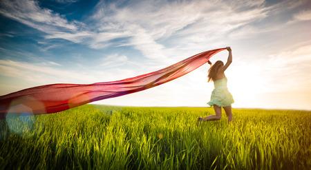 ティッシュ グリーン フィールドで若い女性 runing。幸せ美人夏田舎の牧草地を歩きます。美しいフィット日焼け少女。セクシーなスリムなコーカサ 写真素材