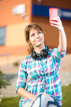Happy young girl taking pictures of herself through cell phone, over collage campus. Selfie woman. photo