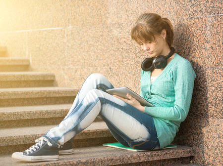 Preparing to exams outdoors. Headphones music. Beautiful young female student writing or reading something from note pad. Woman sitting on stairs in city park. Stock Photo
