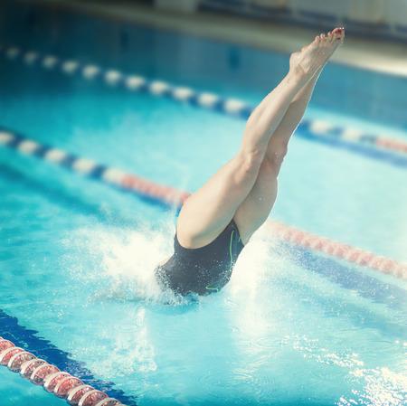 Porträt einer Schwimmerin, dass Springen und Tauchen in Sportinnenpool. Sportliche Frau.