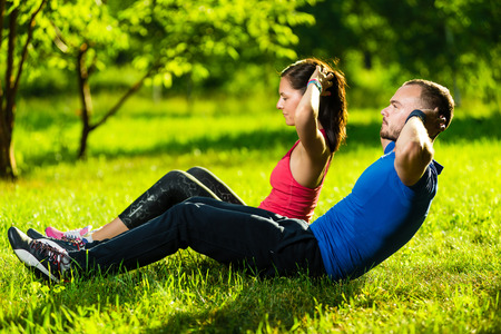 abdominal fitness: El hombre y la mujer el ejercicio en el parque de la ciudad. Hermosa pareja multirracial joven. Siéntese sube la aptitud par de hacer ejercicio al aire libre en la hierba. Montar la gente feliz trabajando al aire libre.