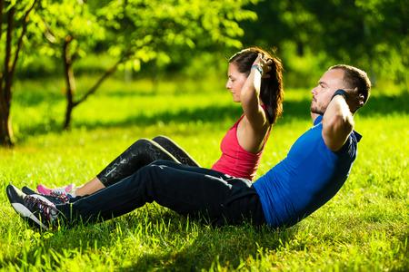 Man och kvinna tränar på stadsparken. Vackra unga raser par. Sit ups fitness par utövar utanför i gräset. Montera glada människor tränar utomhus.