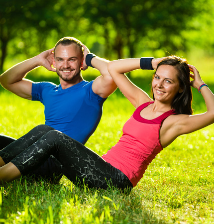 working out: Man and woman exercising at the city park. Beautiful young multiracial couple. Sit ups fitness couple exercising outside in grass. Fit happy people working out outdoor.