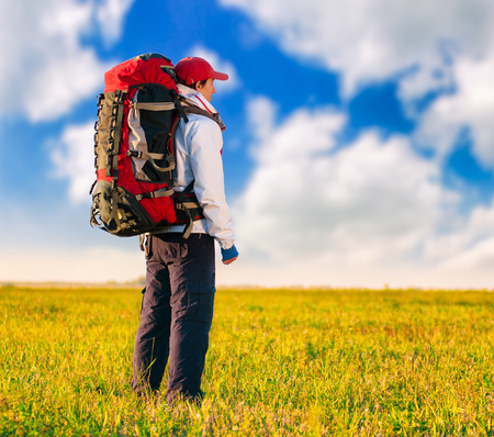 active lifestyle: Hiker with backpack standing in the field. Summer healthy active lifestyle. Single travel.