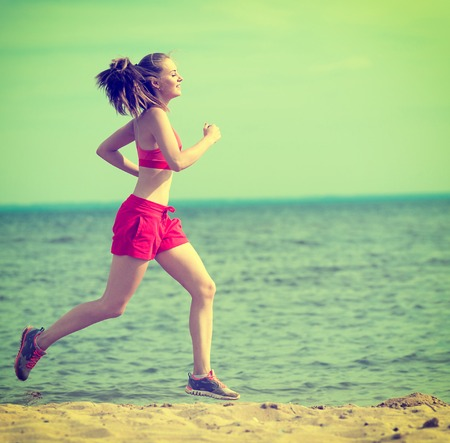 cross process: Young lady running. Woman runner running at the sunny summer sand beach. Workout near ocean sea coast. Beautiful fit girl. Fitness model caucasian ethnicity outdoors. Weight loss exercise. Jogging. Toned, cross process.