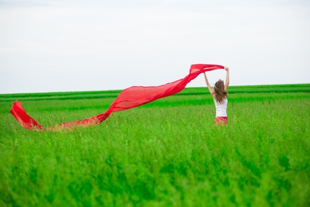 runing: Young lady runing with tissue in green field. Woman and scarf. Stock Photo