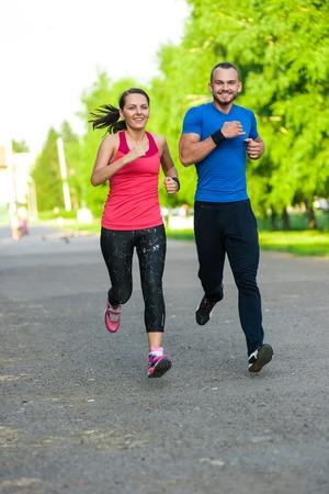 ropa deportiva: Los corredores de entrenamiento al aire libre ejercicio. Ciudad pareja que lleva a correr afuera. Entrenamiento deportivo de la ciudad en el parque verde. Foto de archivo