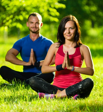 Young man and woman doing yoga in the sunny summer park. Couples Yoga on green grass outdoor. photo