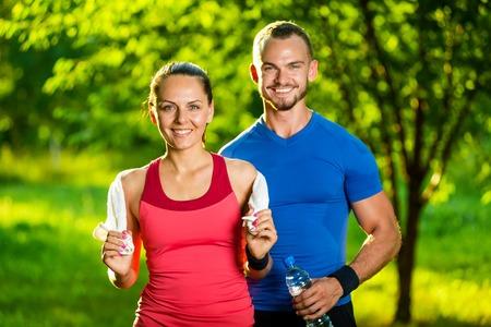 ejercicio: Atlético hombre y la mujer después del ejercicio físico. Hermosa joven pareja en ropa deportiva después de los ejercicios al aire libre. Toalla blanca.
