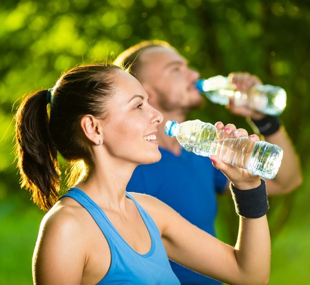 health drink: Man and woman drinking water from bottle after fitness sport exercise. Smiling couple with bottles of cold drink outdoors
