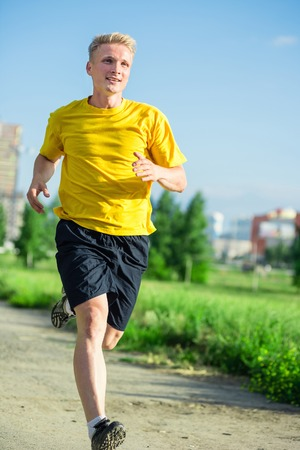 green man: Running man jogging in city street park at beautiful summer day. Sport fitness model caucasian ethnicity training outdoor. Stock Photo