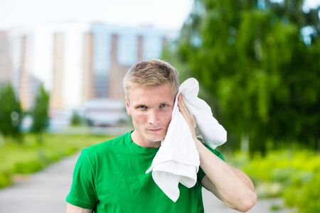 caucasian ethnicity: Tired man with white towel after fitness time and exercising in city street park at beautiful summer day. Sporty model caucasian ethnicity training outdoor.