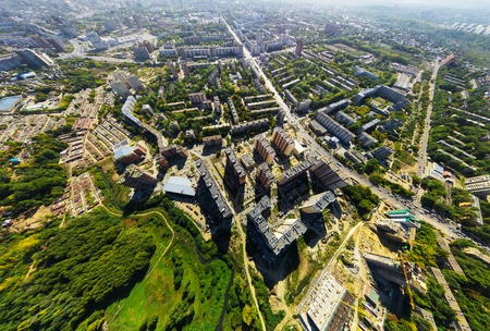 metropolis: Aerial city view with crossroads and roads, houses, buildings, parks and parking lots, bridges. Copter shot. Panoramic image.