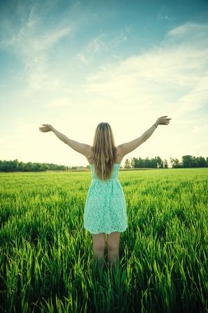 familia orando: Mujer de la felicidad permanecer al aire libre bajo la luz del sol de la puesta del sol. Con las manos levantadas en el momento del amanecer