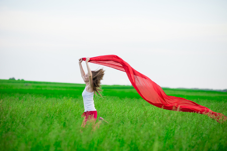 runing: Young lady runing with tissue in green field. Beautiful happy woman walking  in the summer rural meadow