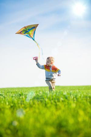 papalote: Muchacho joven que vuela su cometa en un campo abierto. Ni�o jugando con la cometa en el prado verde. Ni�ez. Foto de archivo