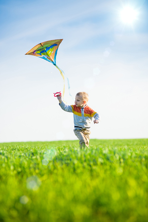 blonde boy: Young boy flies his kite in an open field. Little kid playing with kite on green meadow. Childhood concept. Stock Photo