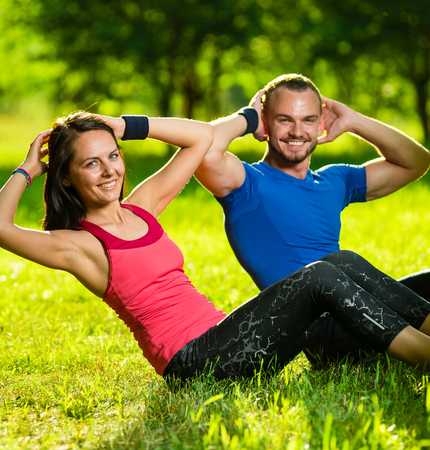 personal trainer: Man and woman exercising at the city park. Beautiful young multiracial couple. Sit ups fitness couple exercising outside in grass. Fit happy people working out outdoor.