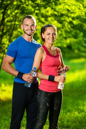 man drinking water: Man and woman drinking water from bottle after fitness sport exercise. Smiling couple with bottles of cold drink outdoors