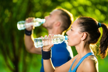 water park: Man and woman drinking water from bottle after fitness sport exercise. Smiling couple with bottles of cold drink outdoors
