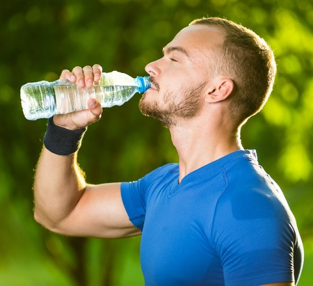 water park: Athletic sport man drinking water from a bottle. Cold drink after outdoor fitness.