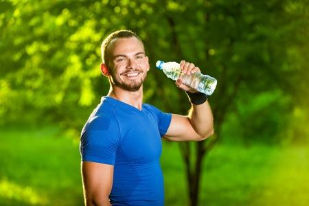 tomando agua: Hombre del deporte atlético beber agua de una botella. Bebida fría después de la aptitud al aire libre.